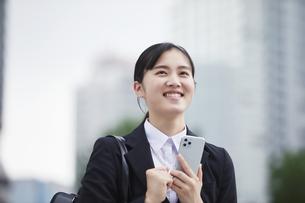 オフィス街でスーツを着てスマートフォンを持つ若い女性の写真素材 [FYI04599069]