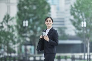 オフィス街でスーツを着てスマートフォンを持つ若い女性の写真素材 [FYI04599072]