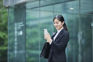 オフィス街でスーツを着てスマートフォンを持つ若い女性の写真素材 [FYI04599074]