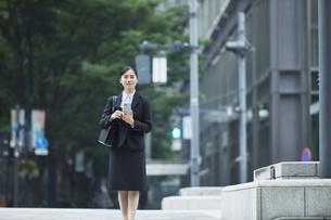 オフィス街でスーツを着てスマートフォンを持つ若い女性の写真素材 [FYI04599076]