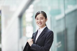 オフィス街でスーツを着たカメラ目線の若い女性の写真素材 [FYI04599080]