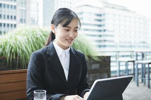 オフィス街のカフェでスーツを着てタブレットPCを持つ若い女性の写真素材 [FYI04599179]