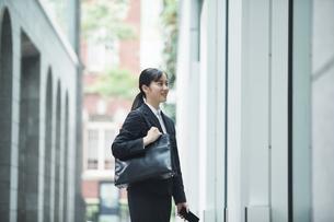 オフィス街でスーツを着てスマートフォンを持つ若い女性の写真素材 [FYI04599182]