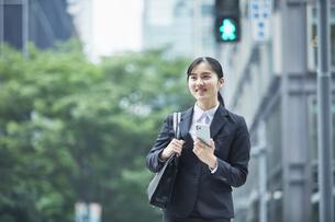 オフィス街でスーツを着てスマートフォンを持つ若い女性の写真素材 [FYI04599183]