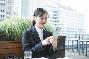 オフィス街のカフェでスーツを着てスマートフォンを持つ若い女性の写真素材 [FYI04599185]