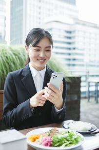 オフィス街のカフェでスーツを着てスマートフォンを持つ若い女性の写真素材 [FYI04599187]