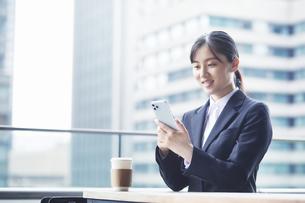 オフィス街のカフェでスーツを着てスマートフォンを持つ若い女性の写真素材 [FYI04599191]