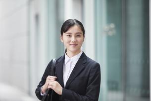 オフィス街でスーツを着た若い女性の写真素材 [FYI04599193]