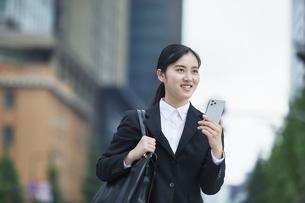 オフィス街でスーツを着てスマートフォンを持つ若い女性の写真素材 [FYI04599195]