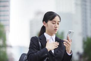 オフィス街でスーツを着てスマートフォンを持つ若い女性の写真素材 [FYI04599198]