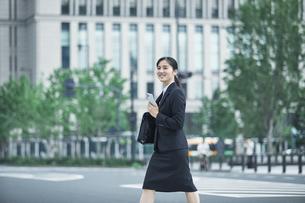 オフィス街でスーツを着てスマートフォンを持つ若い女性の写真素材 [FYI04599201]