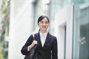 オフィス街でスーツを着て歩く若い女性の写真素材 [FYI04599202]