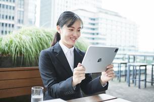 オフィス街のカフェでスーツを着てタブレットPCを持つ若い女性の写真素材 [FYI04599203]