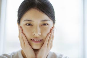 頰に手をあてる若い女性の写真素材 [FYI04599287]
