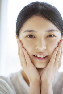 頰に手をあてる若い女性の写真素材 [FYI04599288]