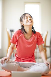 部屋でヨガをする若い女性の写真素材 [FYI04599289]