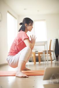 部屋でヨガをする若い女性の写真素材 [FYI04599296]