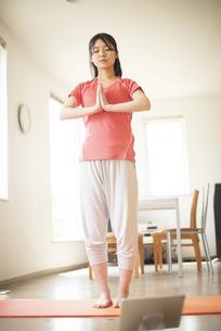部屋でヨガをする若い女性の写真素材 [FYI04599297]