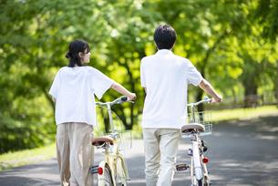 遊歩道で自転車を押すカップルの写真素材 [FYI04599306]