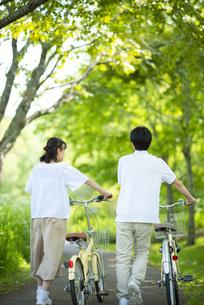 遊歩道で自転車を押すカップルの写真素材 [FYI04599310]