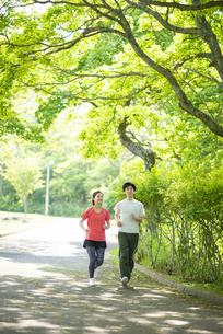 遊歩道でランニングするカップルの写真素材 [FYI04599314]