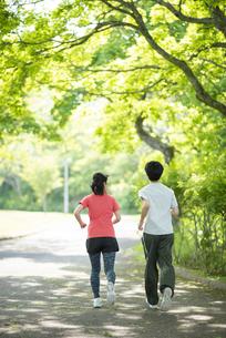 遊歩道でランニングするカップルの後ろ姿の写真素材 [FYI04599315]