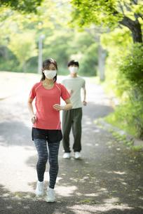 マスクをしながらランニングするカップルの写真素材 [FYI04599321]