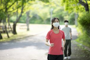マスクをしながらランニングする若い女性の写真素材 [FYI04599323]