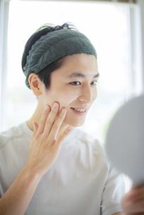 手鏡を見ながら頰に手をあてる若い男性の写真素材 [FYI04599340]