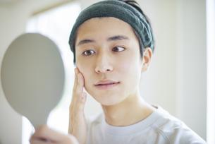 手鏡を見ながら頰に手をあてる若い男性の写真素材 [FYI04599344]