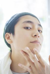 顎に手をあてる若い男性の写真素材 [FYI04599354]