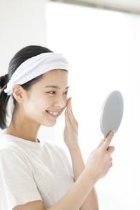 手鏡をのぞく若い女性の写真素材 [FYI04599402]