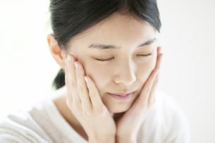 頰に手をあてる若い女性の写真素材 [FYI04599406]