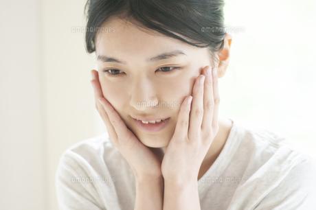 頰に手をあてる若い女性の写真素材 [FYI04599407]