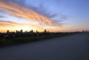 荒川土手のアスファルト道路と朝焼けの川口市の高層タワーマンション群の写真素材 [FYI04601492]