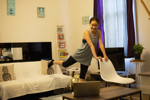 家でパソコンを見ながらエクササイズをしている女性の写真素材 [FYI04601651]