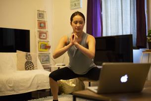 家でパソコンを見ながらエクササイズをしている女性の写真素材 [FYI04601653]