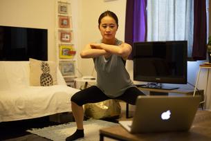 家でパソコンを見ながらエクササイズをしている女性の写真素材 [FYI04601654]