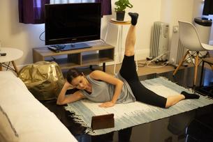 家でタブレットを見ながらエクササイズをしている女性の写真素材 [FYI04601655]