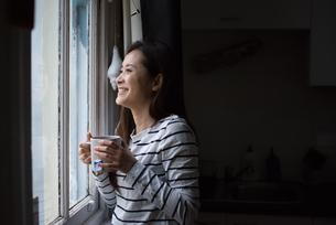 窓辺であたたかい飲み物を持っている女性の写真素材 [FYI04601710]
