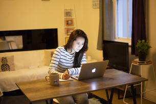 家でパソコンを使って仕事をしている女性の写真素材 [FYI04601728]