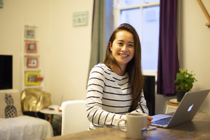 家でパソコンを使って仕事をしている笑顔の女性の写真素材 [FYI04601730]