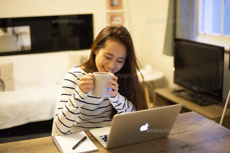 家でカップを持ってパソコンを見ている女性の写真素材 [FYI04601749]