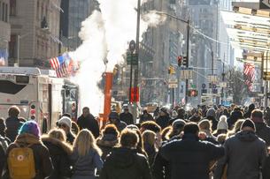 ミッドタウンマンハッタン五番街に漂う蒸気の中を行き交う人々と交通の写真素材 [FYI04601870]