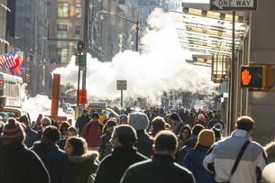 ミッドタウンマンハッタン五番街に漂う蒸気の中を行き交う人々と交通の写真素材 [FYI04601879]