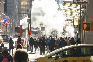 ミッドタウンマンハッタン五番街に漂う蒸気の中を行き交う人々と交通の写真素材 [FYI04601882]