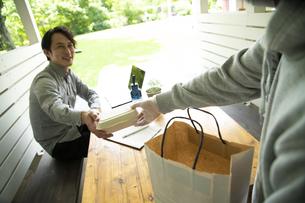 デリバリースタッフからお弁当を受け取るミドルの男性の写真素材 [FYI04601960]