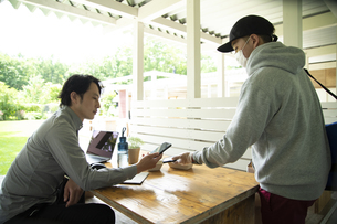 デリバリースタッフとスマホで電子決済するミドルの男性の写真素材 [FYI04601968]