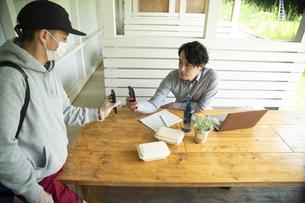 デリバリースタッフとスマホで電子決済するミドルの男性の写真素材 [FYI04601970]