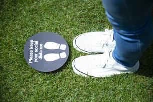 ソーシャルディスタンスマークと若い男性の足元の写真素材 [FYI04601988]